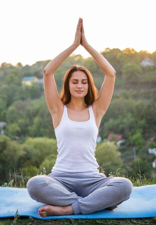 Photo pour pretty young girl sitting in the lotus position with eyes closed and hands over head - image libre de droit
