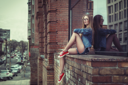 Photo pour Outdoor lifestyle portrait of pretty young sitting girl, wearing in hipster swag grunge style urban background. Retro vintage toned image, film simulation. - image libre de droit