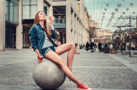 Foto de Outdoor lifestyle portrait of pretty young girl blowing bubble in the city, Wearing in hipster swag grunge style urban background. Retro vintage toned image, film simulation. - Imagen libre de derechos