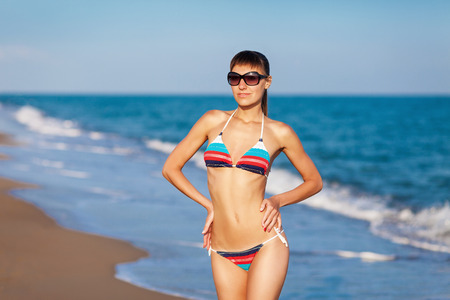 Photo pour Fashion outdoor portrait young sexy lady having fun and posing in striped bikini and sunglasses on sea background. Sunset light. - image libre de droit