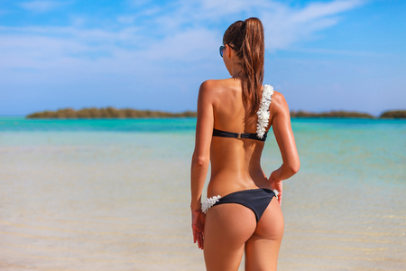 Photo pour Sexy back of enjoying female outdoors on the coast on Red Sea, Egypt. Happy woman in bikini and sunglasses. Luxury travel tourism concept in tropical country. - image libre de droit