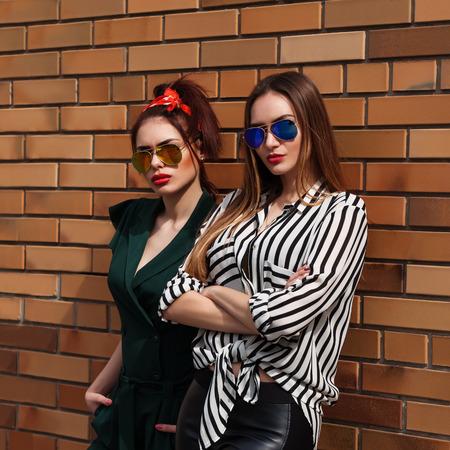 Photo pour Beautiful fashion women posing. Trendy lifestyle urban portrait on city background. - image libre de droit