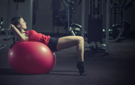 Young, beautiful, sports girl does exercises on a fitball at the gym. Toning.