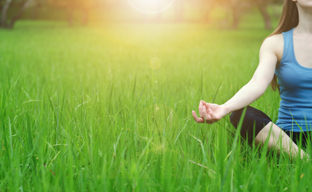 Foto de Closeup of a hand of a young girl who practices yoga in nature. Lotus posture. Sunny highlight falls to hand. Warm toning. - Imagen libre de derechos