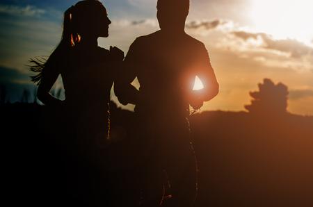 Young couple running at sunset outdoors. Solar flare illuminates a couple back.