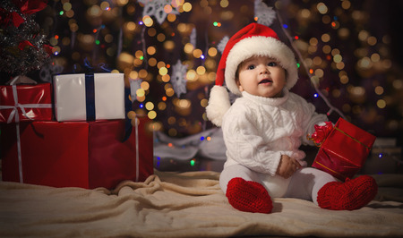 Little smiling boy (baby) in a white knitted sweater and hat of Santa Claus on a background of Christmas garland and gift boxes with ribbon.の写真素材