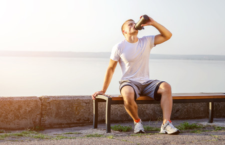 Photo pour young strong Caucasian man with white headphones drinks a protein cocktail from a shaker after running on open air. The bright sun illuminates it. - image libre de droit