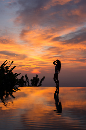 Silhouette of slim woman standing on infinity luxury pool and watching outstanding multicolor sunset.