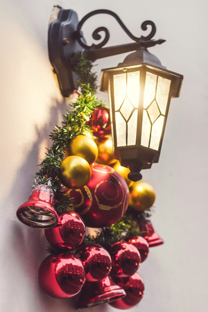 Street lantern decorated for Christmas with beautiful red and golden glass toys. Beaming in night