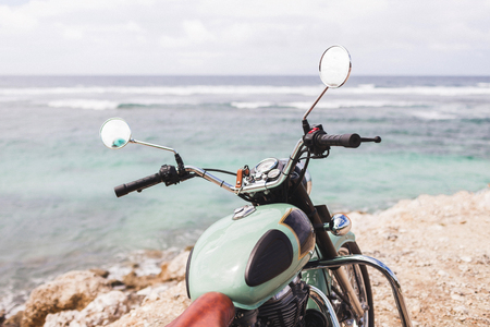 Old vintage motorcycle standing on the edge of cliff with amazing ocean view