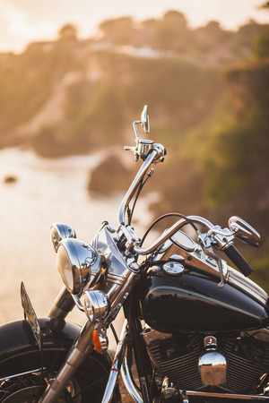 Old vintage motorcycle standing on the edge of cliff in warm sunlight at sunrise, shiny details of bike close-up