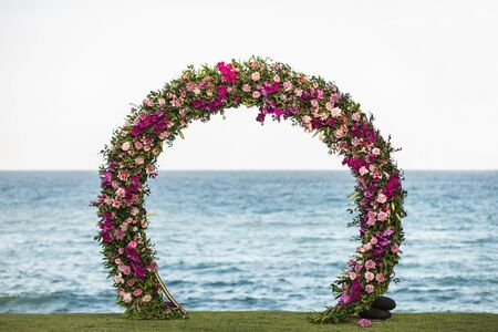 Photo pour Wedding round arch decorated with beautiful colorful orchid and rose flowers on the beach. Ocean on background. - image libre de droit