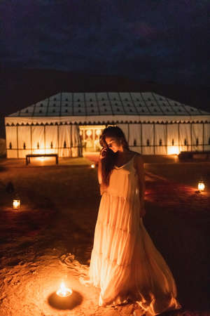 Photo pour Woman in white dress at night near burning candle. Romantic evening in glamping desert camp in Sahara, Morocco. Unusual destination for wedding. - image libre de droit