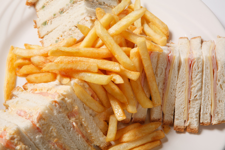Different types of sandwiches with French fries on a white plate. Isolated. Closeup