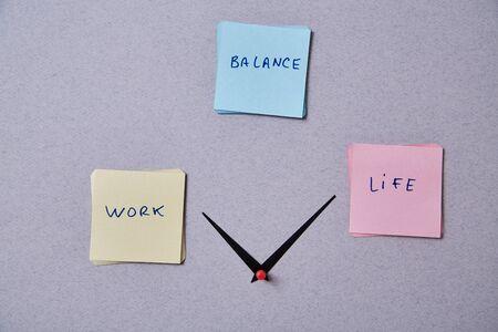 Photo pour Work life balance choice concept. Clock arrows between stickers with inscriptions - image libre de droit