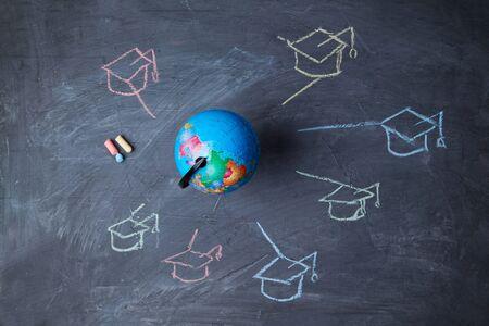 Photo pour Global online education and e-learning. Webinar and language school. Globe, and symbols graduate caps. - image libre de droit