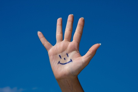 Human palm with smile on blue sky background