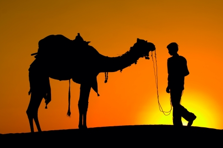 Photo pour Rajasthan village. Silhouette of a man and camel at sunset in the desert, Jaisalmer - India - image libre de droit