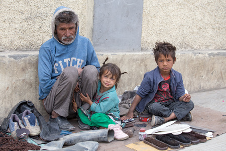 LEH, INDIA - SEPTEMBER 08 2014: An unidentified beggar family begs for money from a passerby in Leh. Poverty is a major issue in India