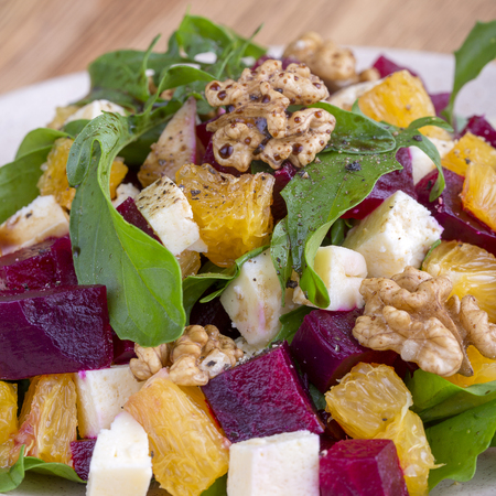 Healthy vegetarian salad with beetroot, green arugula, orange, feta cheese and walnuts on white plate, close up