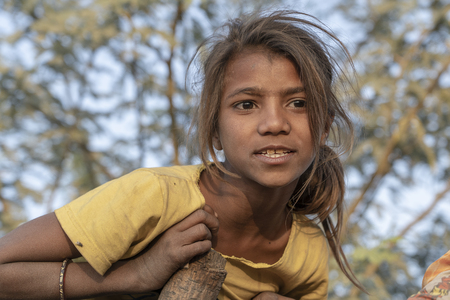 Photo for PUSHKAR, INDIA - NOVEMBER 17, 2018 : Indian young girl in the desert Thar on time Pushkar Camel Mela near holy city Pushkar, Rajasthan, India, close up portrait - Royalty Free Image