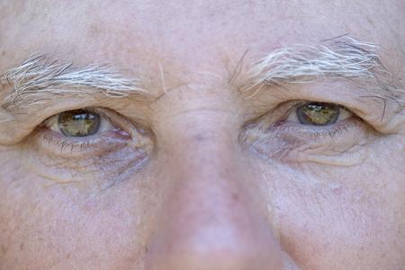 Photo pour Close up eye of caucasian old man. Portrait of old man outdoors. Caucasian male face background, close up eyes, macro - image libre de droit
