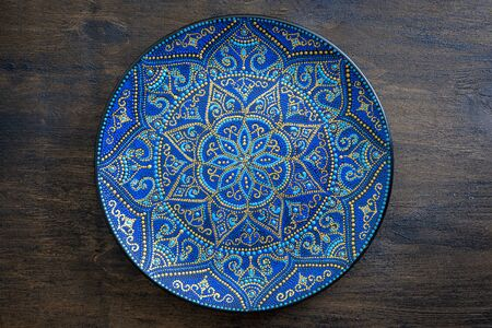 Photo pour Decorative ceramic plate with blue and golden colors, painted plate on wooden background, close up. Decorative porcelain plate painted with acrylic paints, handwork - image libre de droit