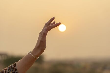 Photo for Silhouette of young girl holding the sun in hand during sunset, close up - Royalty Free Image