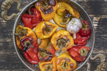 Photo pour Baked red and yellow bell peppers. Peppers in a baking dish on a wooden table. A healthy and delicious vegetarian dish. Close up, top view - image libre de droit