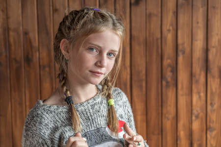 Photo pour Beautiful blonde young girl with freckles indoors on wooden background, close up portrait - image libre de droit
