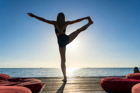 Photo pour Silhouette of woman standing at yoga pose on the tropical beach during sunset. Caucasian girl practicing yoga near sea water - image libre de droit