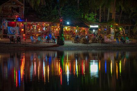Photo pour KOH PHANGAN, THAILAND - MAY 03, 2019: Beach bar, coconut palm trees, sea water and night club is reflected in seawater at tropical island Koh Phangan, Thailand - image libre de droit