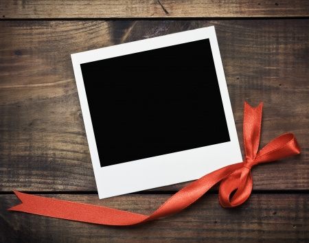 photo frame with a red bow on a wooden background