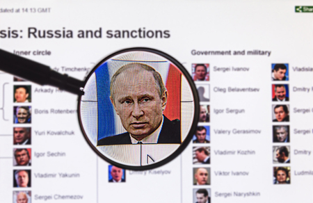 Moscow, Russia - January 31, 2015: Photo of President Putin on the background of the sanctions list through a magnifying glass at the site of News BBS. BBC News is an operational business division of the British Broadcasting Corporation