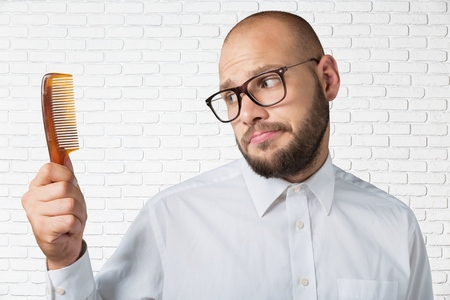 Bald man holding a comb