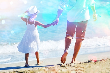 Rear view of father and son holding hands while walking on sand at beach