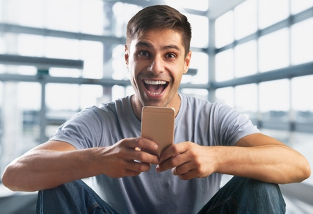 Heppy young man looking at mobile