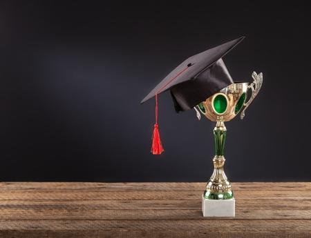 Photo pour graduation cap with champion golden trophy on wood table with copy space ready for your design.graduation, success, education, concept - image libre de droit