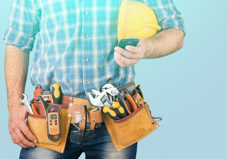 Close-up of construction worker sending text on mobile phone