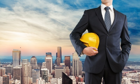 Young business man in suit holding yellow helmet on city background