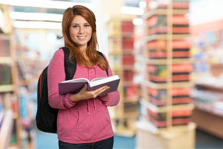 Woman student reading book on library background