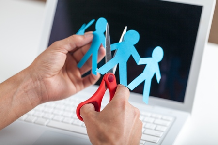 Closeup of Hands Cutting Paper People on Laptop