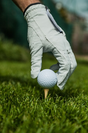 Hand with Glove Placing Golf Ball on a Tee