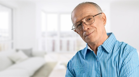 Senior man in blue shirt and glasses