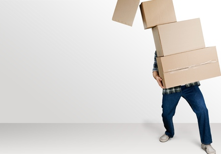 Photo for Delivery man carrying stacked boxes in front of face against white background - Royalty Free Image