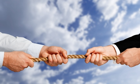 Business men hands holding rope on grey background