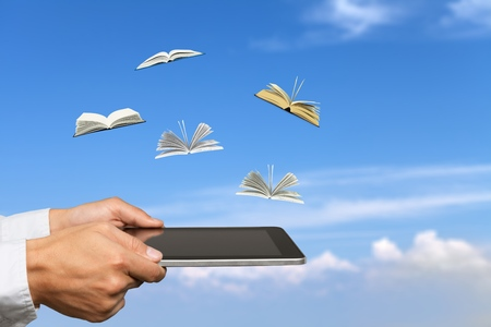 Male's hands holding digital tablet with flying little books