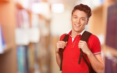 Young handsome student on blurred library background
