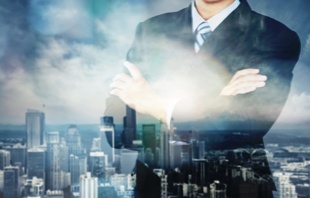 Young handsome businessman on blurred cityscape background