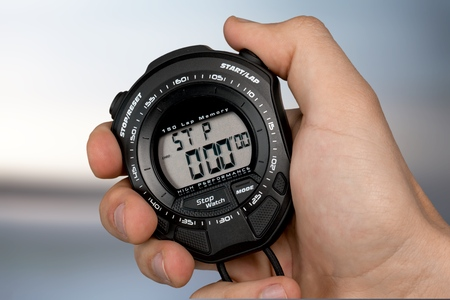 Male hand holding stopwatch on blurred background